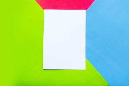 Papier blanc vierge sur fond de papier géométrique rouge, bleu et vert. Espace de copie pour le texte Banque d'images