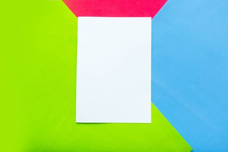 White paper blank on red, blue and green geometric paper background. Copy space for the text Imagens