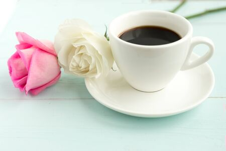 Coffee cup and roses on wooden table