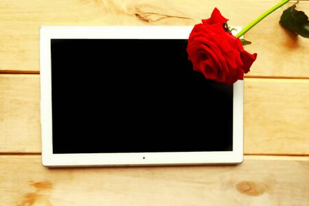Black mockup tablet and red rose on wooden background. Valentines Day greeting card