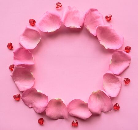 Frame of pink rose petals on pink background. Copy space for the text. Valentines Day greeting card Reklamní fotografie
