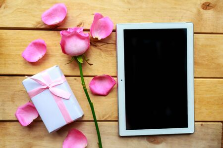 Love composition - rose, gift box and mockup black tablet on wooden background. Valentines Day greeting card