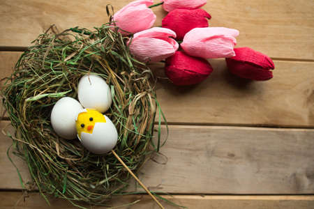 Flat lay photo with chicken eggs and toy chicken in straw nest and bouquet of tulips. Easter concept. Copy space Imagens