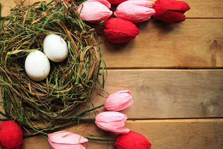 Flat lay photo with eggs in straw nest and bouquet of tulips on wooden background. Easter concept. Copy space Imagens