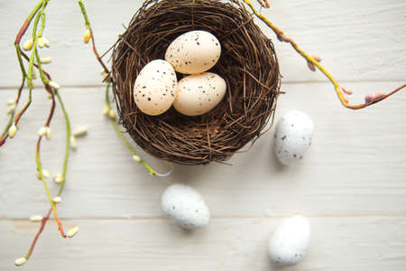 quail eggs in the nest, top view, wooden background, Easter concept
