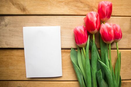 Pink tulips and white mockup blank on wooden background. Flat lay, top view, copy space. Womens Day or Mothers Day greeting card