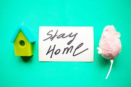 Toy house and the card with message Stay Home on green background. Quarantine concept