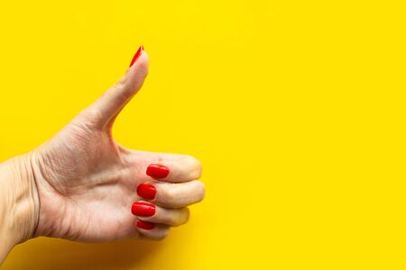 Woman's hand shows the super gesture over bright yellow background. Minimal concept. Copy space for the text