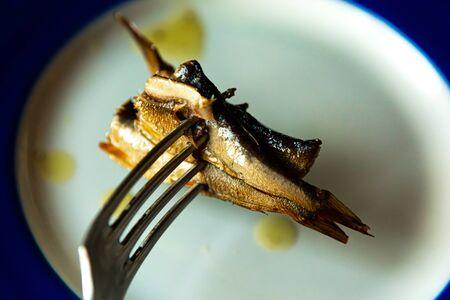 sprat in oil impaled on a fork, closeup