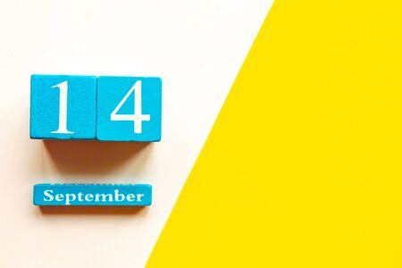 September 14, empty yellow and white geometric background. Wooden handmade calendar