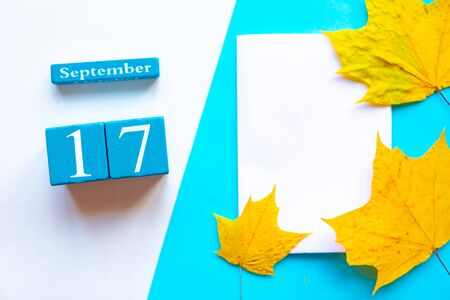 September 17. Wooden handmade calendar and white mockup blank with dry maple leaves on geometric white and blue background
