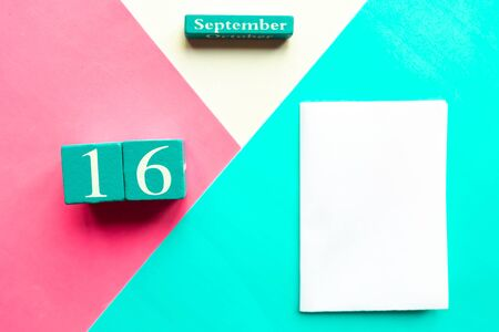 September 16. Wooden handmade calendar and white mockup blank on geometric white, pink and blue background