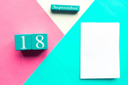 September 18. Wooden handmade calendar and white mockup blank on geometric white, pink and blue background