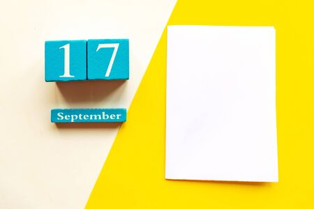 September 17, empty yellow and white geometric background and white mockup blank. Wooden handmade calendar
