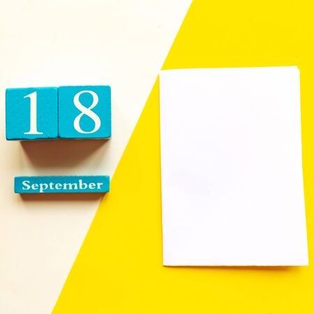 September 18, empty yellow and white geometric background and white mockup blank. Wooden handmade calendar