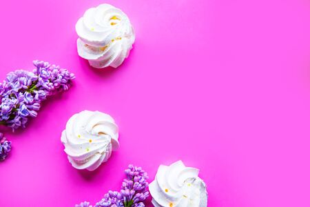 Tasty fresh meringue and blooming lilac on bright pink background, top view, copy space for the text