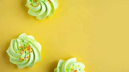 Tasty fresh meringue on yellow background, top view, copy space 스톡 콘텐츠