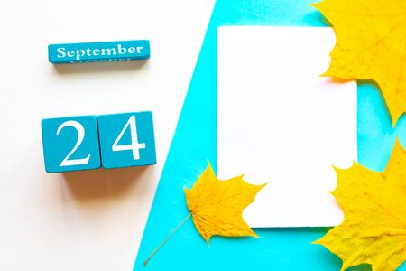 September 24. Wooden handmade calendar and white mockup blank with dry maple leaves on geometric white and blue background
