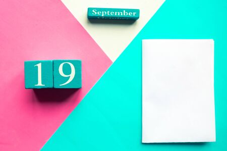 September 19. Wooden handmade calendar and white mockup blank on geometric white, pink and blue background