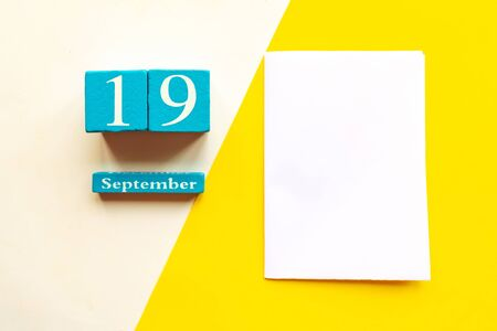 September 19, empty yellow and white geometric background and white mockup blank. Wooden handmade calendar