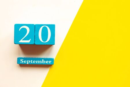 September 20, empty yellow and white geometric background and white mockup blank. Wooden handmade calendar