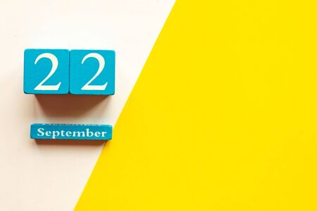 September 22, empty yellow and white geometric background and white mockup blank. Wooden handmade calendar 스톡 콘텐츠
