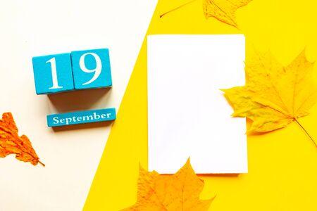 September 19, empty yellow and white geometric background. Wooden handmade calendar