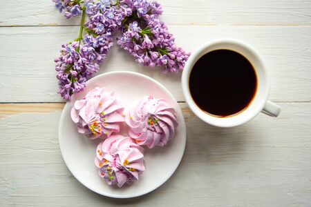 Tasty meringue, coffee cup and lilac blooming branch on wooden table. Flat lay, top view 스톡 콘텐츠
