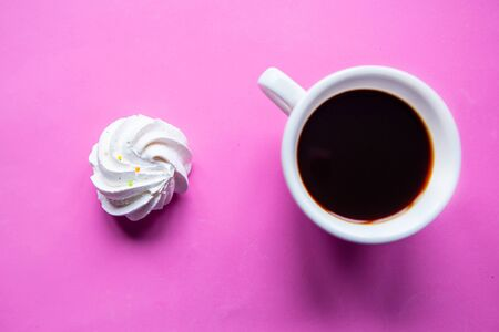 Tasty fresh meringue and coffee cup on bright pink background, top view