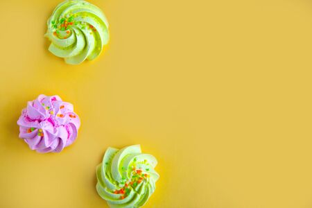 Tasty fresh meringues on yellow background, top view, banner, copy space for the text
