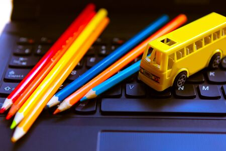 Color pencils and toy school bus on the keyboard on the keyboard. Back to school concept