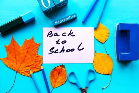 School supplies, maple leafs and card with message Back to School on bright blue background. Flat lay, top view 스톡 콘텐츠