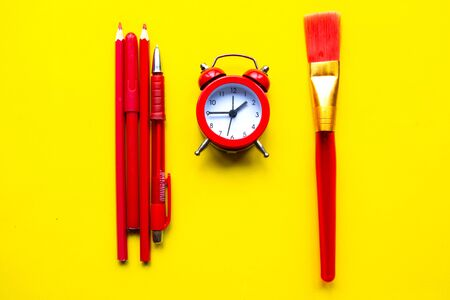 Pencils, alarm clock and paintbrush on bright yellow background. Back to school concept. Minimal concept 스톡 콘텐츠