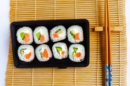 Set of sushi rolls and Chinese chopsticks on sushi mat background, top view 스톡 콘텐츠