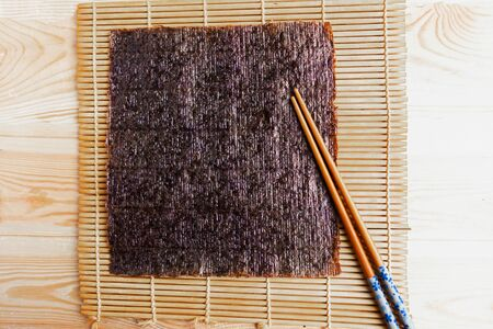 Chinese chopsticks and sushi mat with seaweed background. Copy space for the text