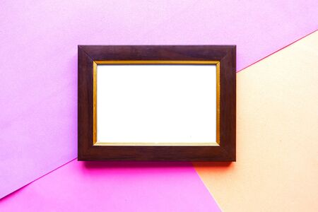 Wooden photo frame on geometric pink background. Copy space for the text