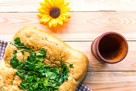 Fresh tasty home baked loaf of bread with parsley on wooden background