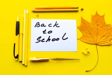 School supplies and card with message with the text Back to School on bright yellow background. Education concept