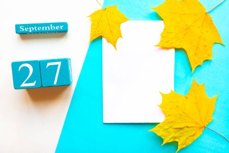 September 27. Wooden handmade calendar and white mockup blank with dry maple leaves on geometric white and blue background
