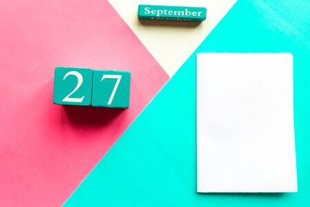 September 27. Wooden handmade calendar and white mockup blank on geometric white, pink and blue background