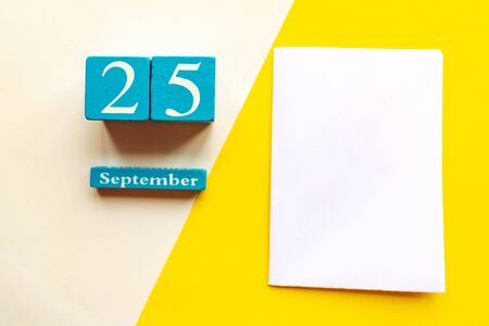 September 25, empty yellow and white geometric background and white mockup blank. Wooden handmade calendar