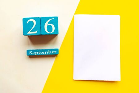 September 26, empty yellow and white geometric background and white mockup blank. Wooden handmade calendar