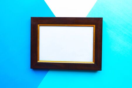 Wooden photo frame on geometric blue background. Copy space for the text 스톡 콘텐츠