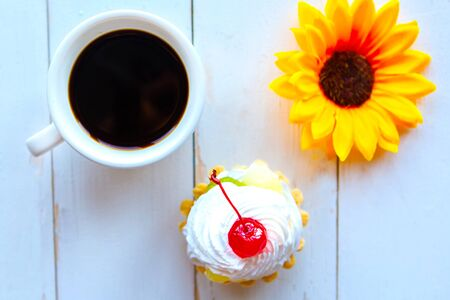 Flat lay photo with fresh cake, bright flower and coffee cup on wooden background 스톡 콘텐츠