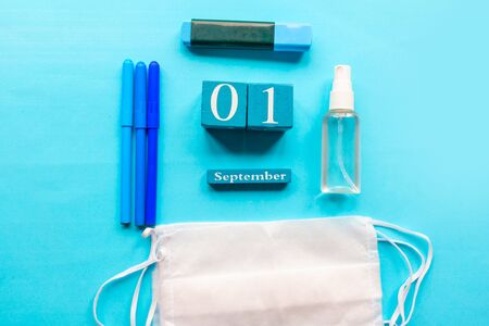 School supplies, hand sanitizer and medical mask on blue background. School quarantine concept