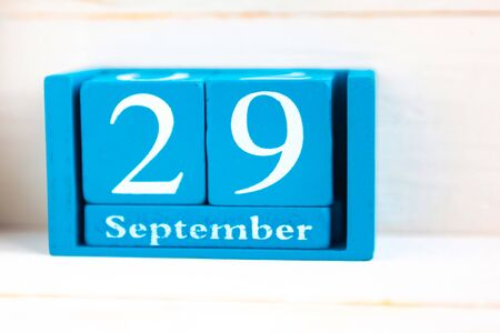 September 29, wooden background. Handmade wooden cube calendar with date month and day