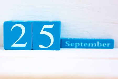 September 25, wooden background. Handmade wooden cube calendar with date month and day