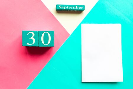 September 30. Wooden handmade calendar and white mockup blank on geometric white, pink and blue background Zdjęcie Seryjne
