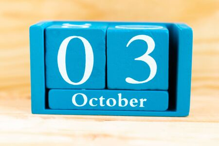 October third. Blue cube calendar with month and date on wooden background.