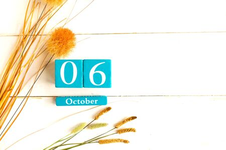 October the 6th. Blue cube calendar with month and date on wooden background. Copy space for the text
